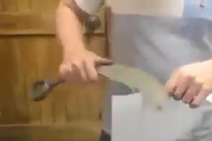 Man making very sharp knife with wrench