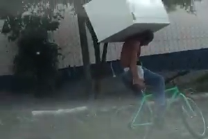 Man picked up a fridge on his shoulders and going on cycle